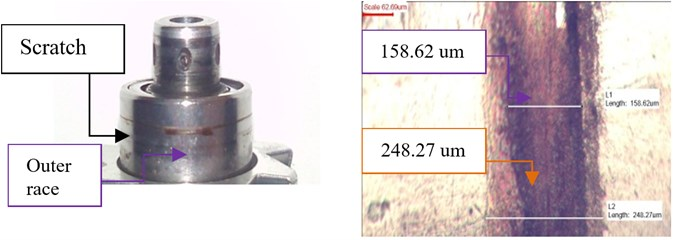 Picture of the damaged outer race bearing with indicated scratch and measured length