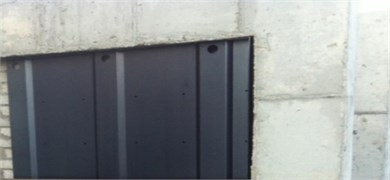 Installation of waved steel panels to concrete frame