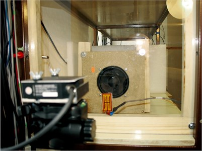 a) The experimental setup and b) the laser triangulation head used  to emulate the laser microphone and the actuating element