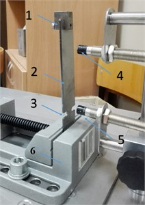 View of testing stand (1 – weight, 2 – specimen, 3 – notch,  4 – upper eddy current sensor, 5 – lower eddy current sensor, 6 – spindle)