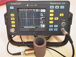 a) EMAT transducer coupled with a popular standard UT instrument MS335 and  b) the manual EMAT thickness measurement performed on boiler tubes
