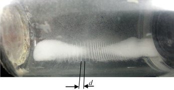 Photos of levitating microparticles on the vibrating cylinder wall nodal sections  at different excitation frequencies: a) 2.44 kHz, b) 14.2 kHz