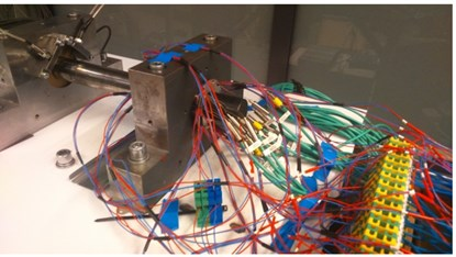 a) Thermoelectric modules and temperature sensors integrated into the bearing bush;  b) general view of the test rig and its control system