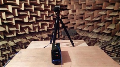 Device during vibroacoustic test in anechoic chamber:  a) rear view of the device, b) side view of the device