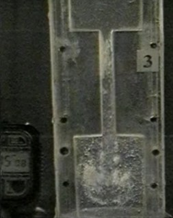 Photograph of a transparent channel with liquid at the moment of drawing the liquid into the pulsation chamber: the appearance of a cavitation cavity and cavitation bubbles at an oscillation frequency of 20 Hz