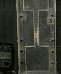 Photograph of a transparent channel  with liquid at the moment of expulsion of the  liquid from the pulsation chamber: the appearance of a cavitation cavity at an oscillation  frequency of 20 Hz